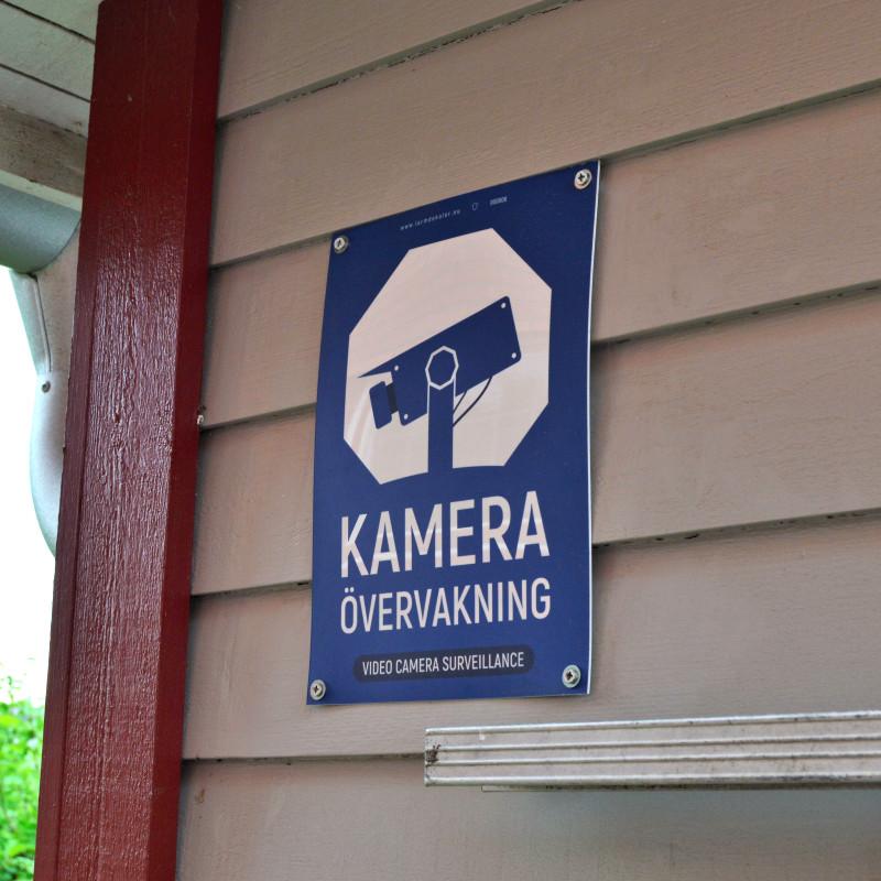 Kameraövervakningsskylt blå med vår egen design monterad med skruv på träfasad